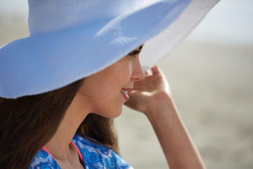 Mujer en la playa con un sombrero para prevenir el cáncer de piel