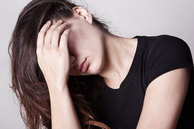 Mujer que padece fuertes dolores de cabeza