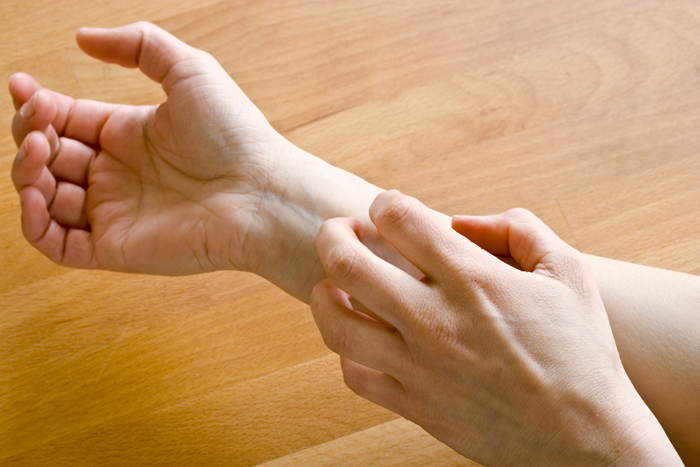 Mujer rascando su brazo