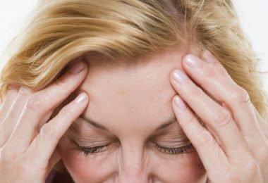 una mujer se realiza masajes en la sien para calmar el dolor de cabeza