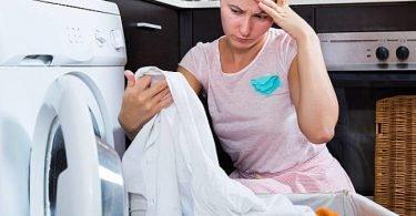 Mujer lavando la ropa en su lavadora para quitar las manchas y blanquearla