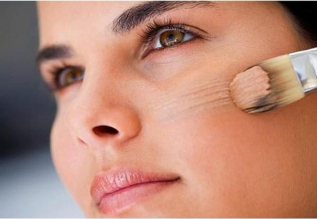 Mujer aplicando maquillaje vencido sobre sus pómulos