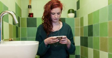 Mujer usando su telefono en el baño
