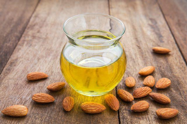 taza con aceite vegetal de almendras para la piel grasa