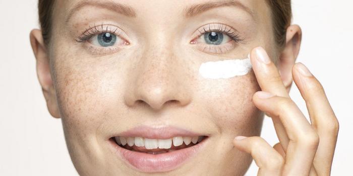 Mujer aplicándose una crema barata en su piel