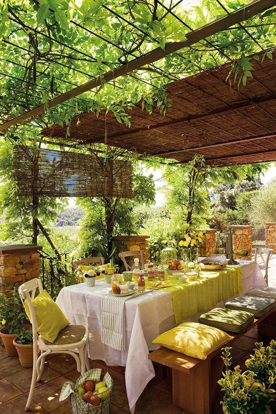una mesa para invitados con la decoración de las enredaderas en el patio de una casa de campo