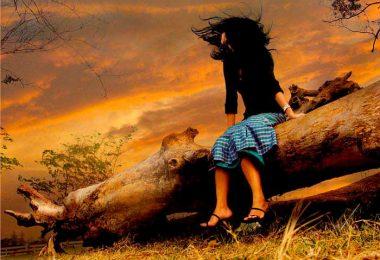 Mujer contemplando el atardecer con un gesto de decepción