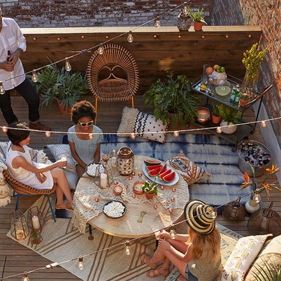 Reunión de amigos en la azotea decorada con estilo bohemio, con mesas y velas, tardeada y merienda en la terraza de la azotea.