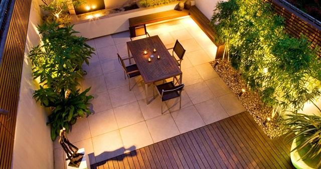 espacio en la azotea iluminado con piso cerámico y madrea, luces y jardineras.