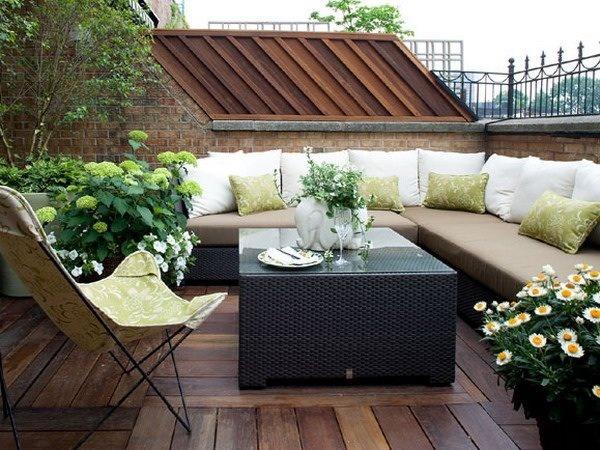 lindo detalle de terraza en la azotea decorado con muebles rústicos y cojines blancos con piso de madera y jardineras laterales.