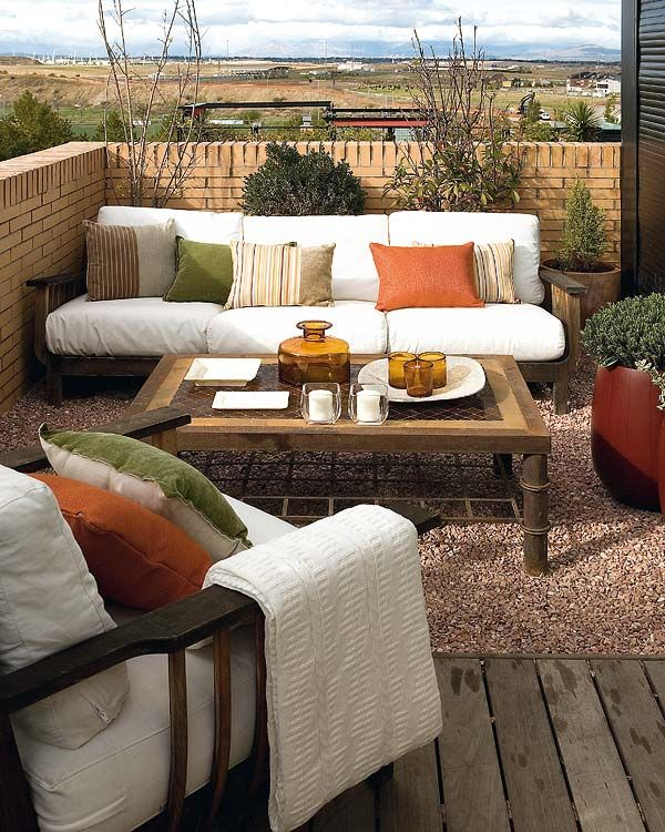 diseño rústico en la azotea de la casa con muebles de madera blancos y mesa, pisos de piedra y madera