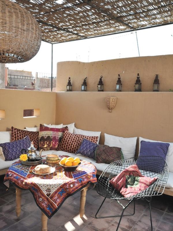 Espacio en la azotea estilo mediterráneo con cojines y tapetes decorados y una techumbre natural