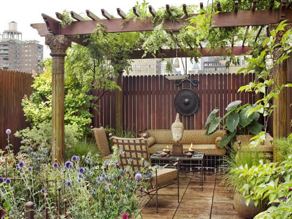 Espacio decorado edn la azotea con estilo rústico con jardineras y una pequeña salita con pérgolas
