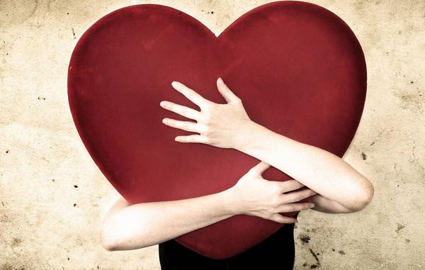 mujer abrazando un corazón