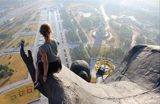 mujer sentada a gran altura sobre una estatua