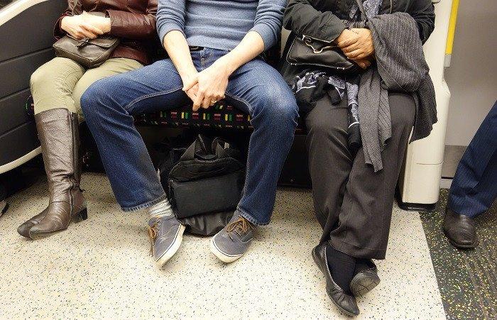 hombre sentado con las piernas demasiado abiertas