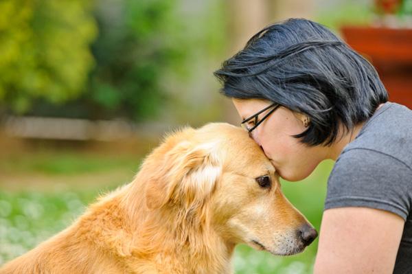 mujer besando en la frente a su mascota