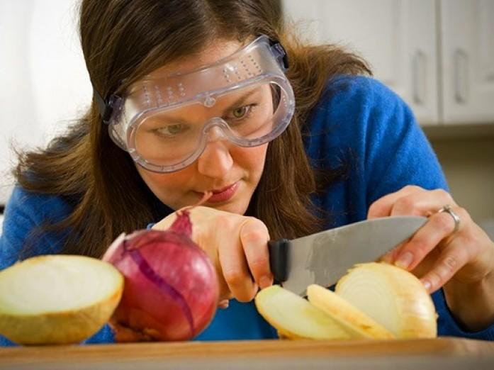 mujer con gafas para evitar llorar mientras corta las cebollas