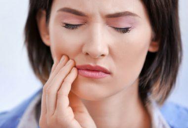 Una mujer afectada por el bruxismo que tiene dolores de cabeza y en la mandíbula