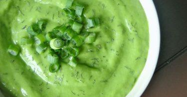 Un plato con deliciosa sopa alcalinizante de pepinos y aguacate con cebollines decorando