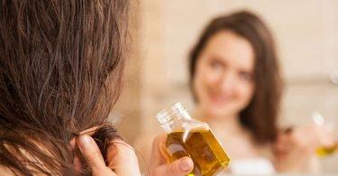 Mujer aplicando aceite de germen de trigo en su cabello