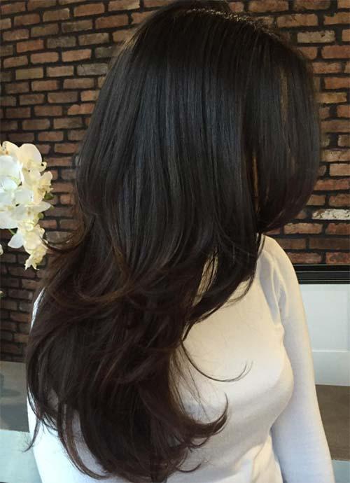 Mujer con cabello castaño oscuro con un corte a capas en cabello largo
