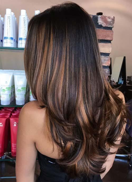 Chica con el cabello oscuro cortado en capas con mechas balayage en tonos cobre