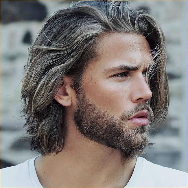 Hombre lleva un corte de cabello medio largo con toques platinados y barba