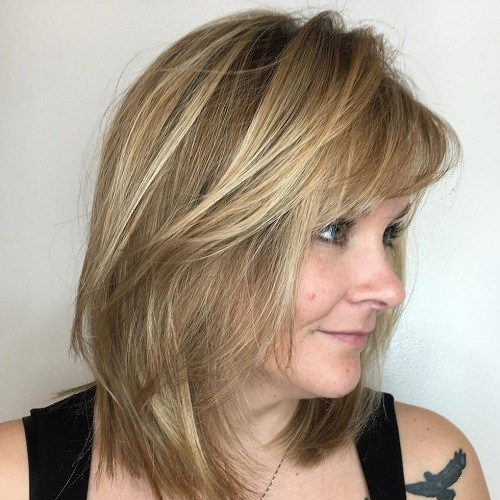 flequillo en cabellera rubia peinado hacia atrás y no lleva apartado