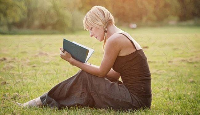 Una mujer leyendo frases y pensamientos positivos en un libro
