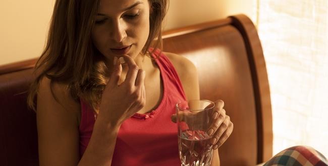Una mujer tomando la pastilla del día después