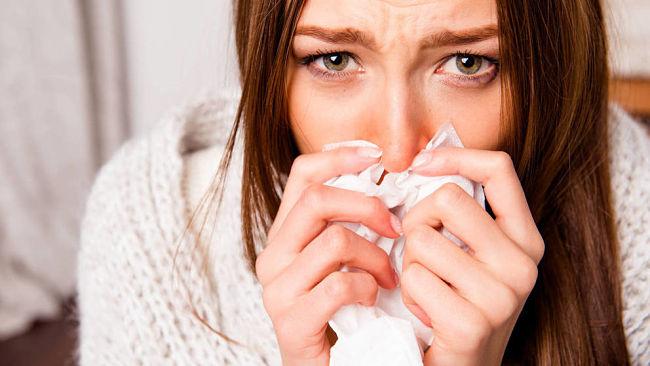 Mujer con síntomas de resfriado que puede complicarse con riesgo de bronquitis