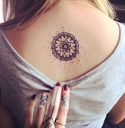 Chica joven que lleva un tatuaje con forma de mandala en su espalda