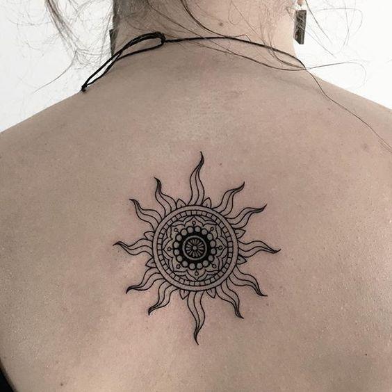 La forma de un sol como un tatuaje en la espalda