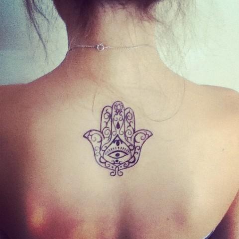 Un tatuaje maori pequeño en la espalda de un mujer