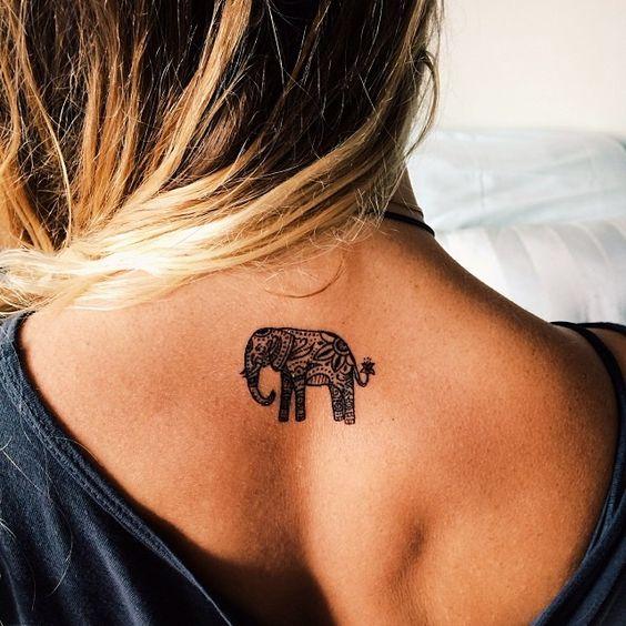Un elefante mediano tatuado entre los omóplatos en la espalda