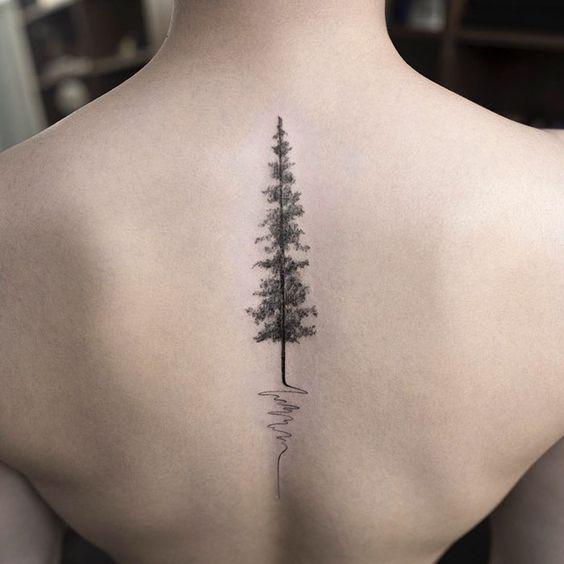 Un pino como un tatuaje en la parte media de la espalda de una joven mujer