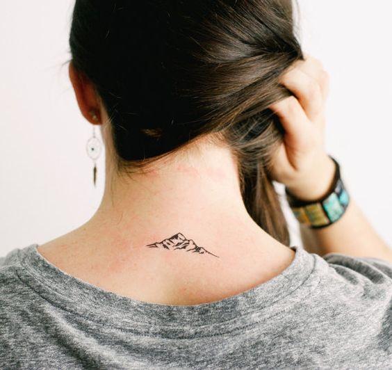 Una chica que lleva una pequeña montaña tatuada en su espalda