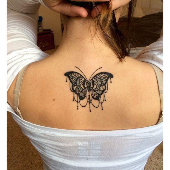 Mariposa de tamaño mediano tatuada en la espalda