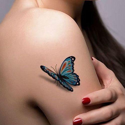 Mujer con una mariposa azul con diseño en 3d tatuada en el brazo