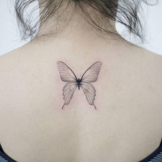 Una mariposa transparente tatuada en la espalda