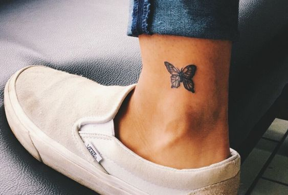 un tatuaje pequeño de una mariposa cerca del tobillo
