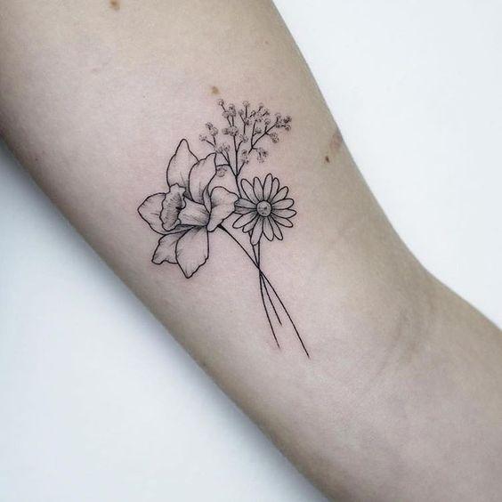 Un conjunto de flores tatuadas en el brazo