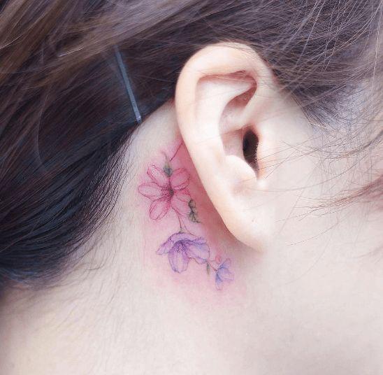 Pequeña rosa tatuada detrás de la oreja