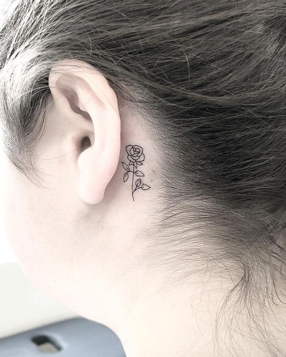 Una flor tribal tatuada detrás de la oreja