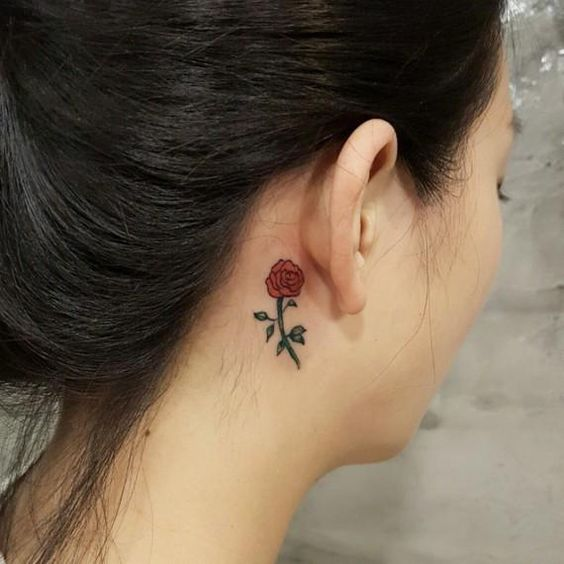 Un tatuaje de una rosa tatuada detrás de la oreja