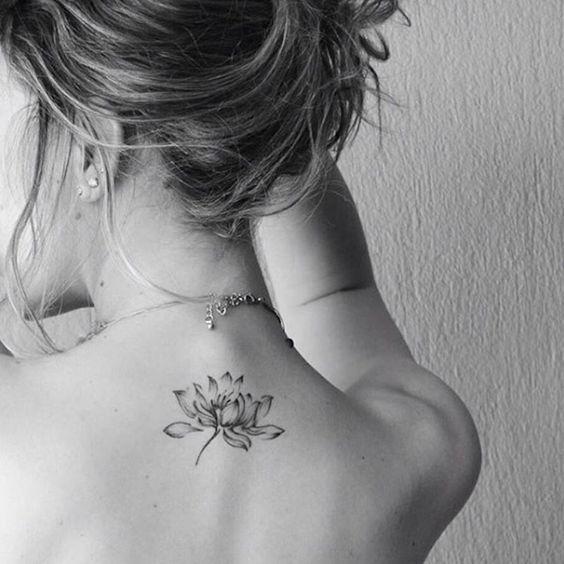 Una flor elegante tatuada en la espalda de una mujer