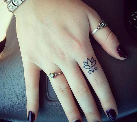 Un tatuaje diminuto de una rosa en el dedo de la mano