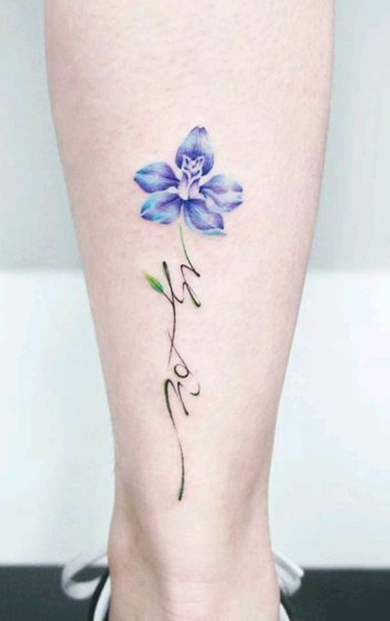Flor de color azul tatuada en la parte baja de la pierna
