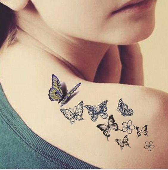 varias mariposas tatuadas en la espalda y hombro de una mujer
